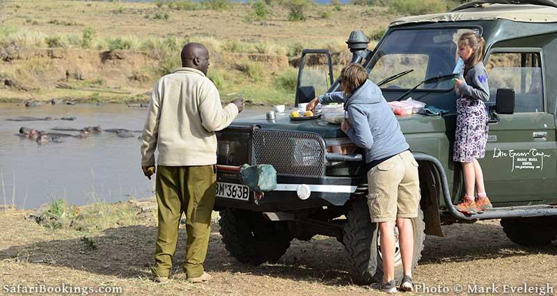 African Safari Guide making snack stop near Hippos