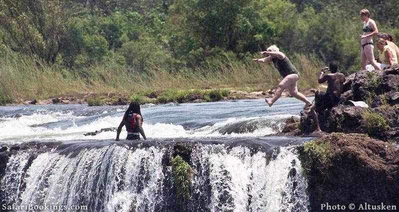 Tourists jumping into Devil's Pool, Victoria Falls