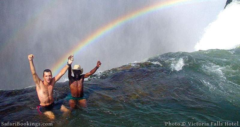 Tourists in Devil's Pool, Victoria Falls with rainbow