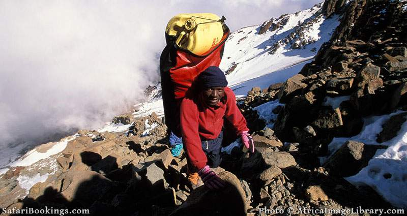Porter carrying luggage to Kibo Crater campsite, Kilimanjaro National Park, Tanzania