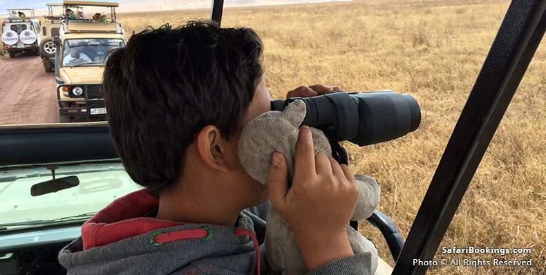 Kid looking through binoculars with stuffed rhino at Ngorongoro Crater