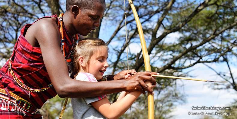 Girl shooting bow and arrow with Masai warrior