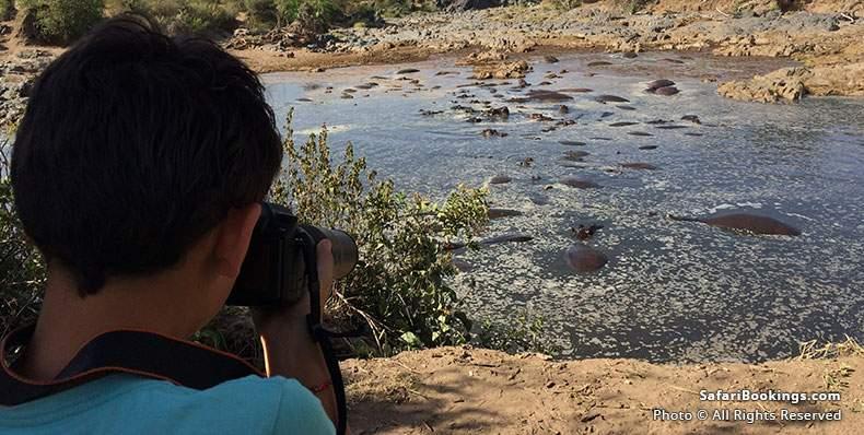 Boy with photo camera at Hippo pool at Serengeti National Park
