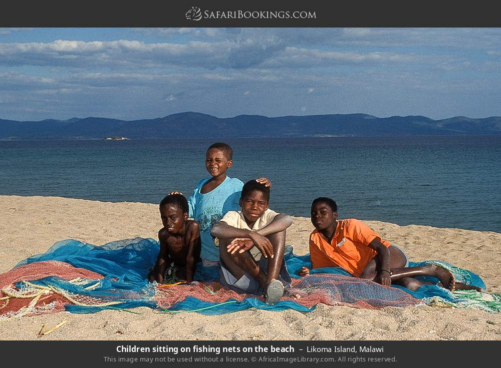 Children sitting on fishing nets on the beach in Likoma Island, Malawi