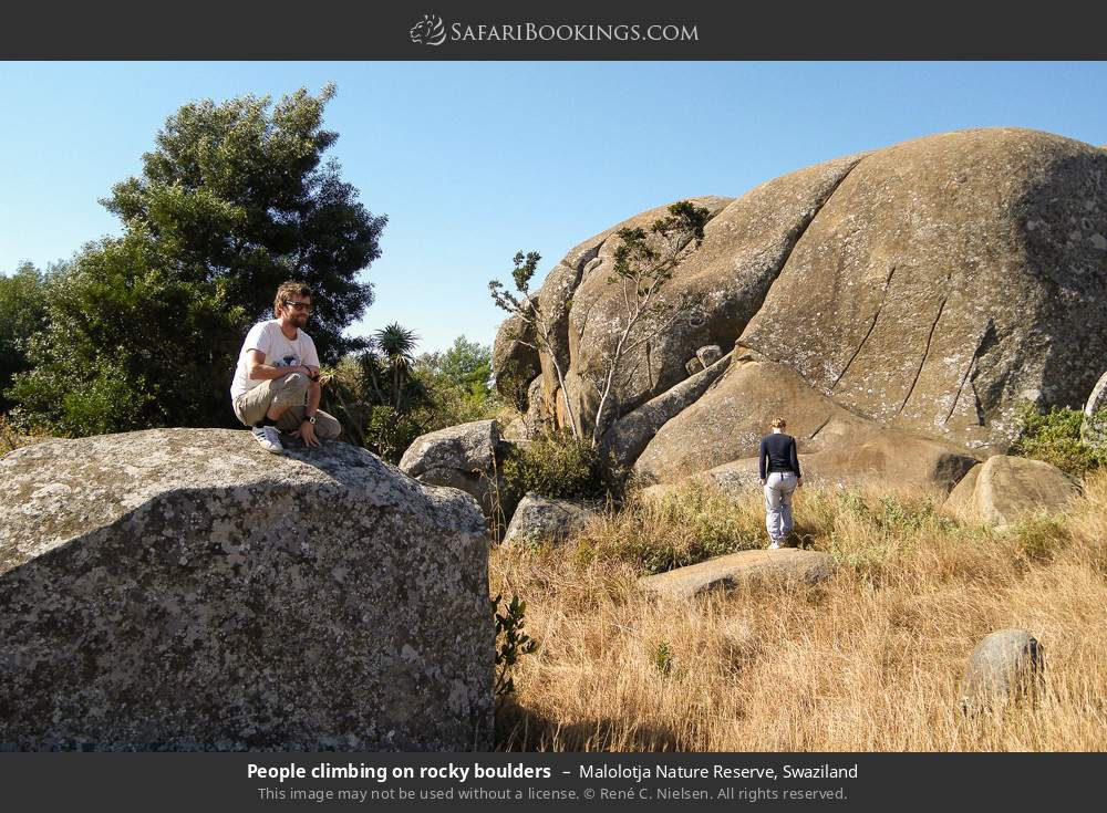 Tourists climbing on rocky boulders in Malolotja Nature Reserve, Swaziland